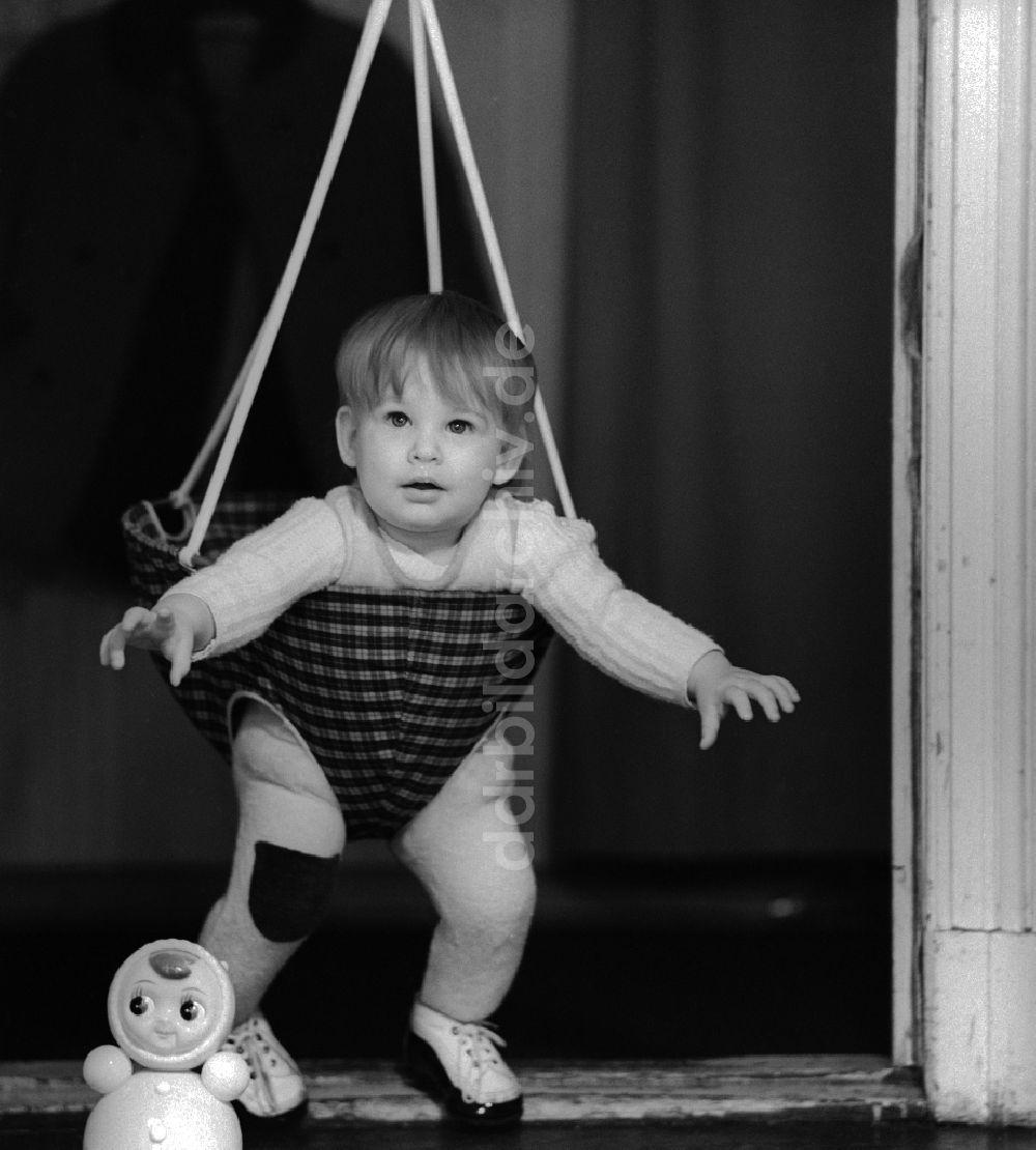 Berlin: Kleinkind in einer Babyschaukel die in einem Türrahmen ...